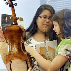 In a Monday, April 9, 2012 photo, Dayani Sanchez, 12, left, and Kathryn Dull, 11, right, talk about the Violins of Hope exhibit at UNC Charlotte in Charlotte, N.C.. Eighteen violins recovered from the Holocaust and restored by  Israeli violin maker Amnon Weinsten make their U.S. debut on Sunday, April 15. Some were played by Jewish prisoners in Nazi concentration camps, while others belonged to the Jewish Klezmer musical culture. (AP Photo/Chuck Burton)