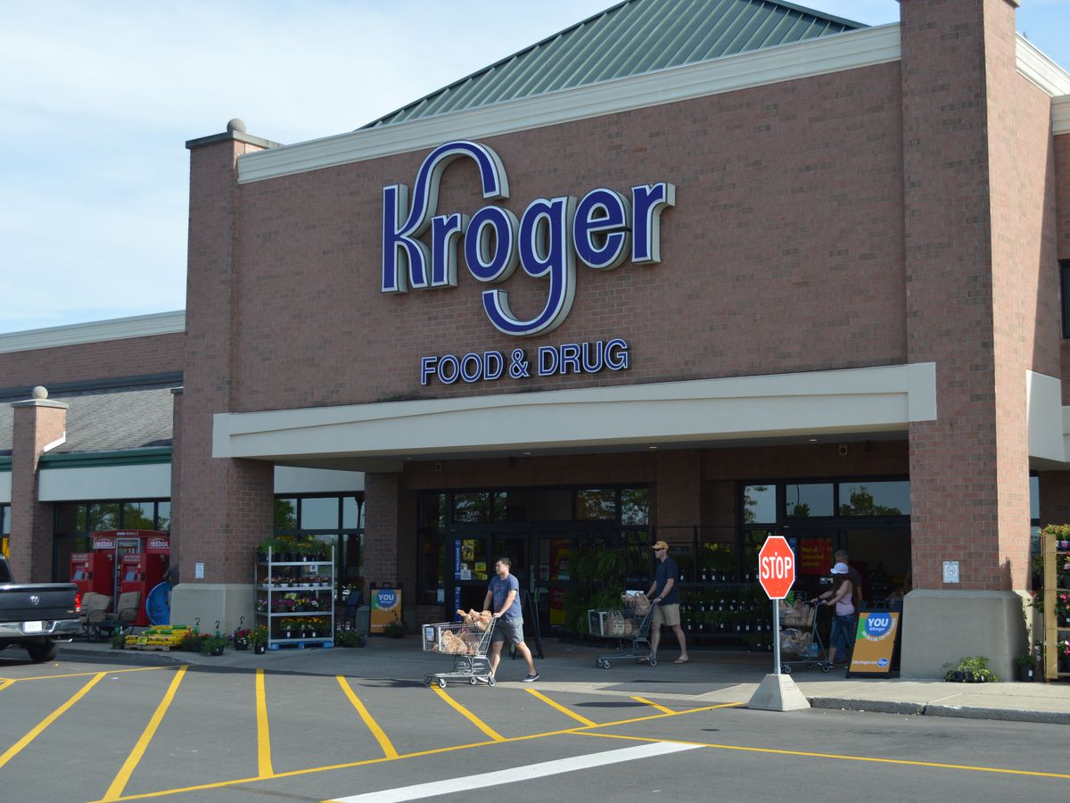The exterior of a supermarket. The facade is red brick. There is a large sign above the entrance that reads: Kroger Food and Drug.