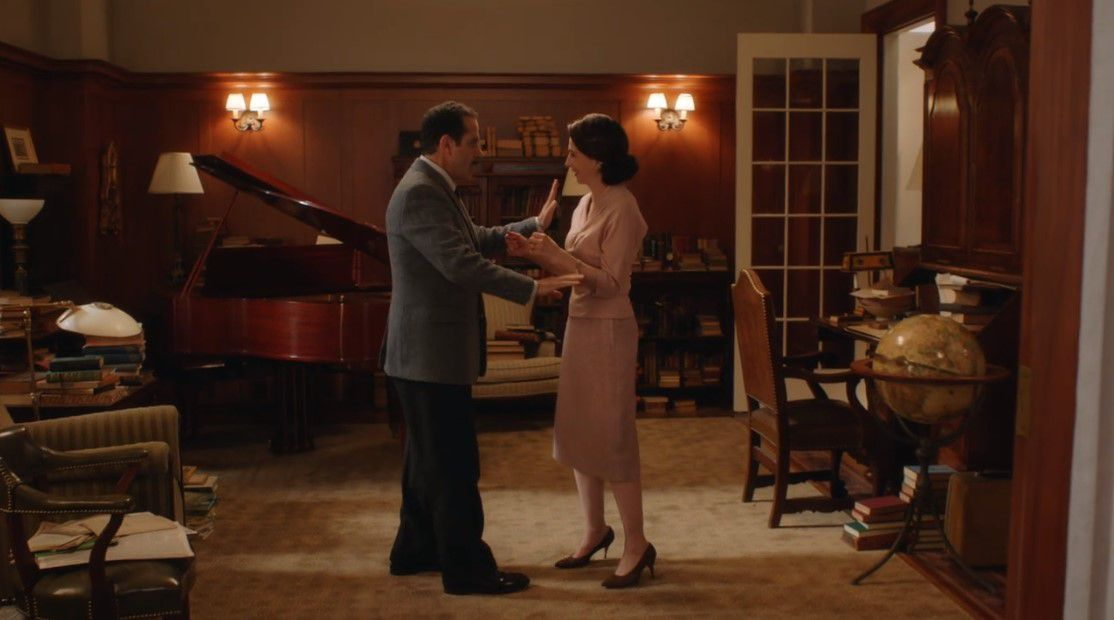 A man and woman dance in a wood-paneled room.