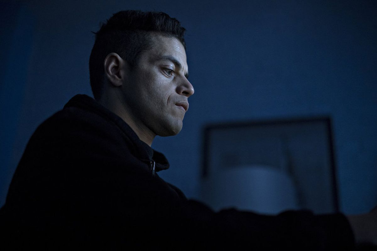 """Rami Malek as Elliot Alderson in the TV show """"Mr. Robot"""" sits and looks at a computer screen."""