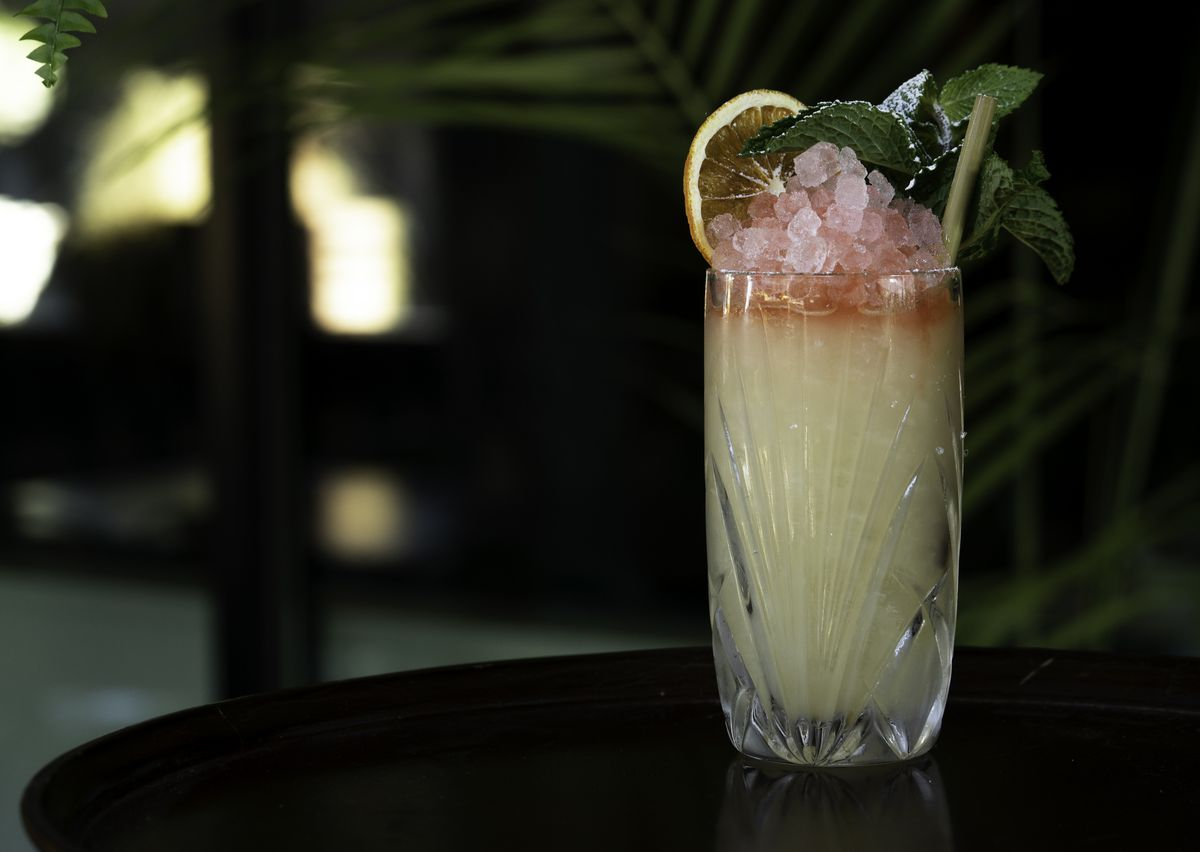 A photo of the Satsuma Mai Tai on a black table garnished with an orange wedge and mint leaves