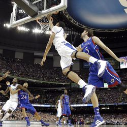 Kentucky's Anthony Davis, center, drives to the basket past Kansas' Jeff Withey during the NCAA championship game.