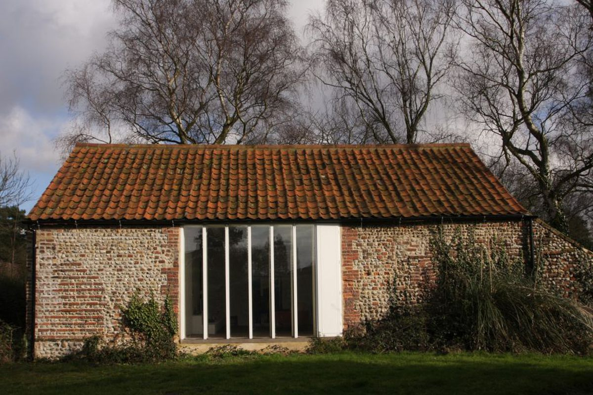 Old brick barn with large central slatted window in white.
