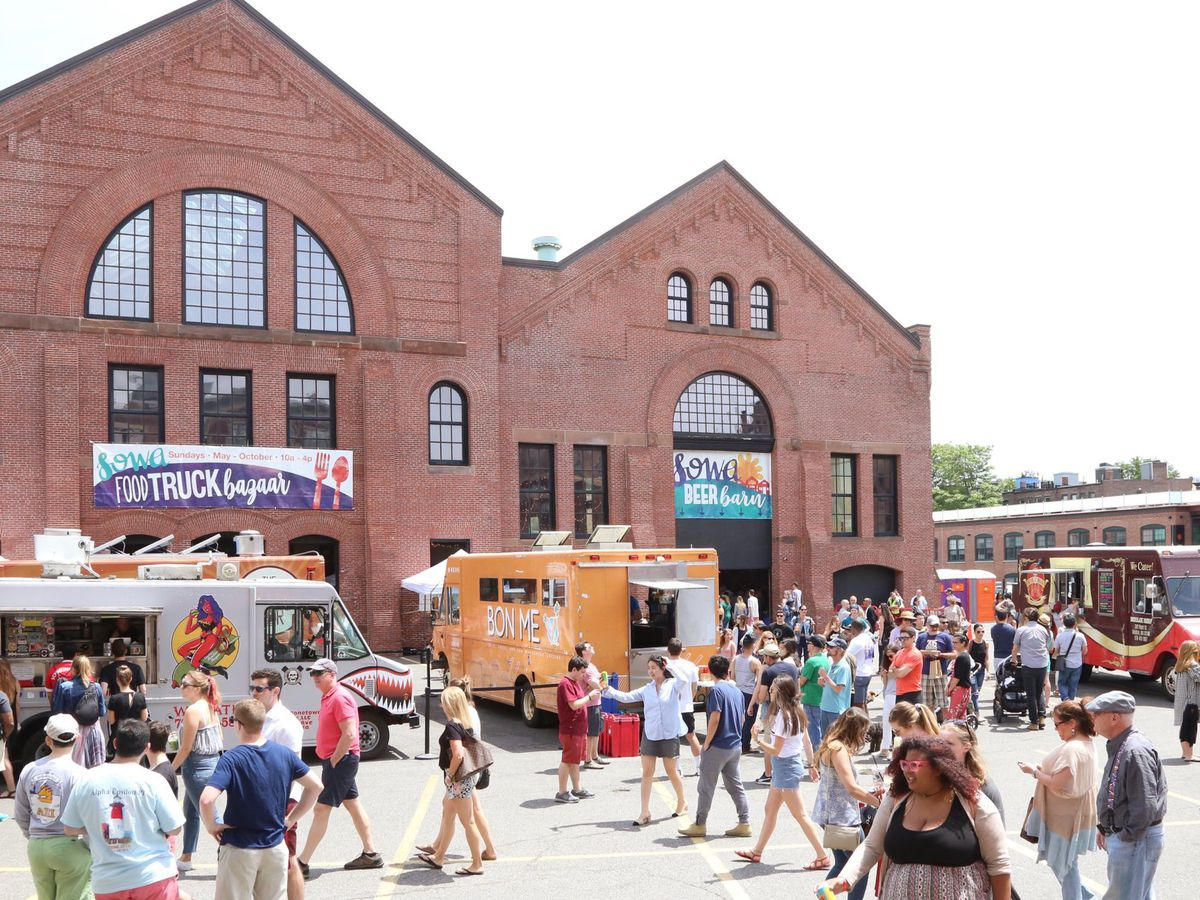 SoWa Market attendees mingle outside a large brick building. There are some food trucks parked in the area, too.