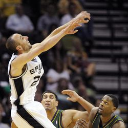 San Antonio Spurs' Manu Ginobili, left, of Argentina, shoots over Utah Jazz's C.J. Miles, right, and Enes Kanter during the first half of an NBA basketball game, Sunday, April 8, 2012, in San Antonio.
