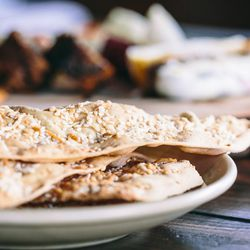 Crisp, sesame-topped lavash is a sturdy vehicle for pate, pickles, and terrine.