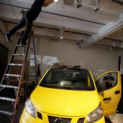 A technician adjusts lighting above the  prototype of a Nissan NV 200 New York City taxi, in New York, Monday, April 2, 2012. The iconic New York City taxi has gotten a passenger-friendly makeover from Nissan with low-annoyance horns, USB chargers and germ-fighting seats to cut down on bad odors. Medallion owners will be required to buy the Nissan NV 200 at a cost of about $29,000 starting in late 2013.