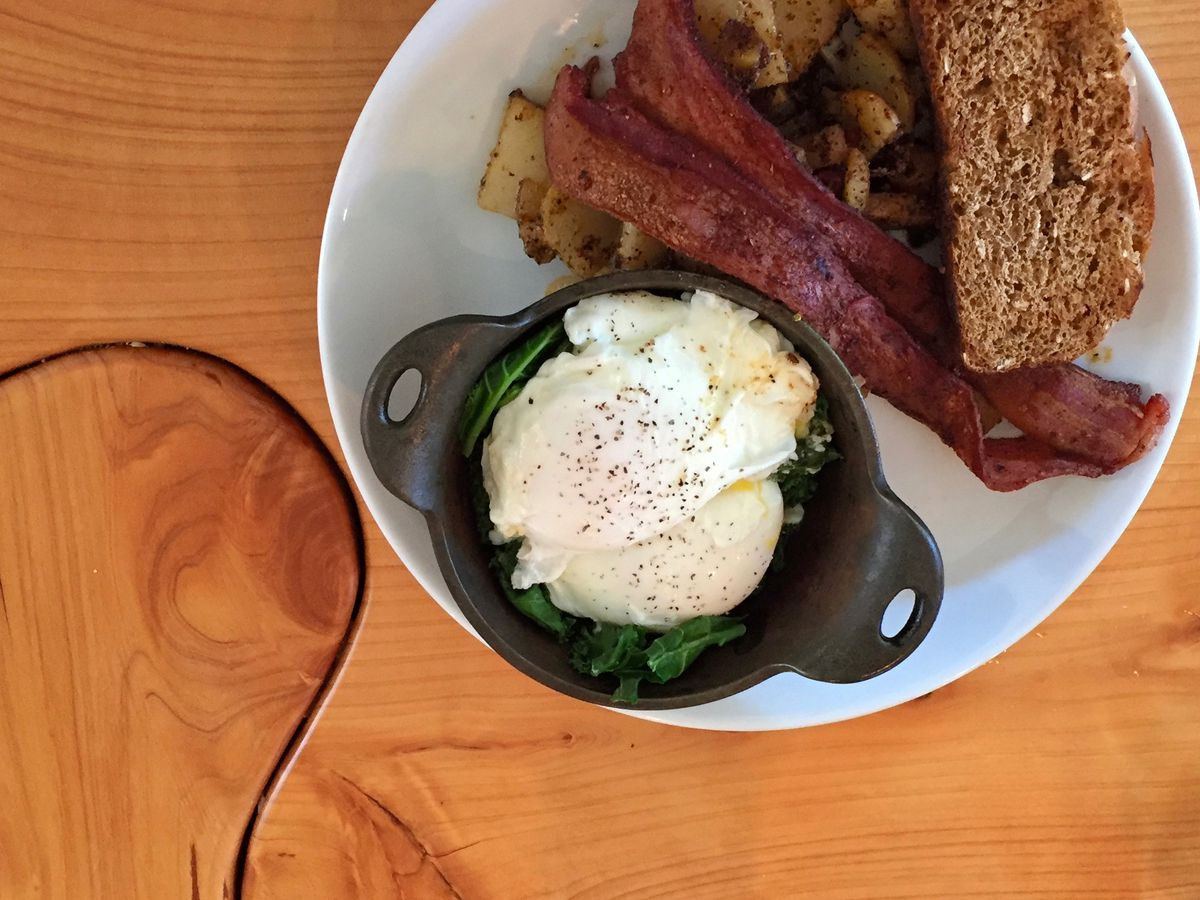 Poached eggs over cooked greens in a tiny pot on a plate with whole-grain toast, bacon, and fried potatoes.
