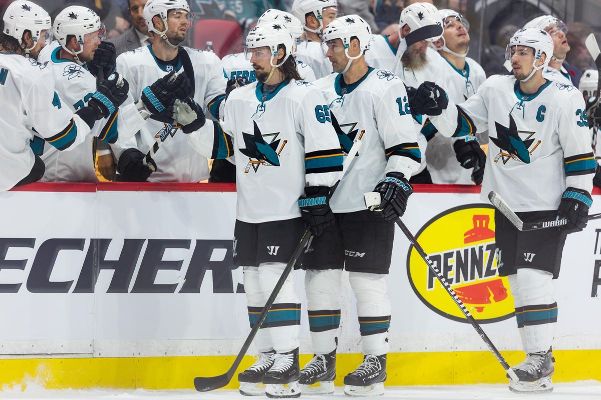 Defenseman Erik Karlsson, center Patrick Marleau and center Logan Couture skate by the bench to celebrate a goal during the second period between the San Jose Sharks and Ottawa Senators on October 27, 2019, at Canadian Tire Centre in Ottawa, ON, Canada.