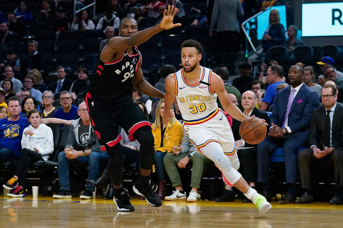 Golden State Warriors guard Stephen Curry drives past Toronto Raptors center Serge Ibaka during the third quarter at Chase Center.