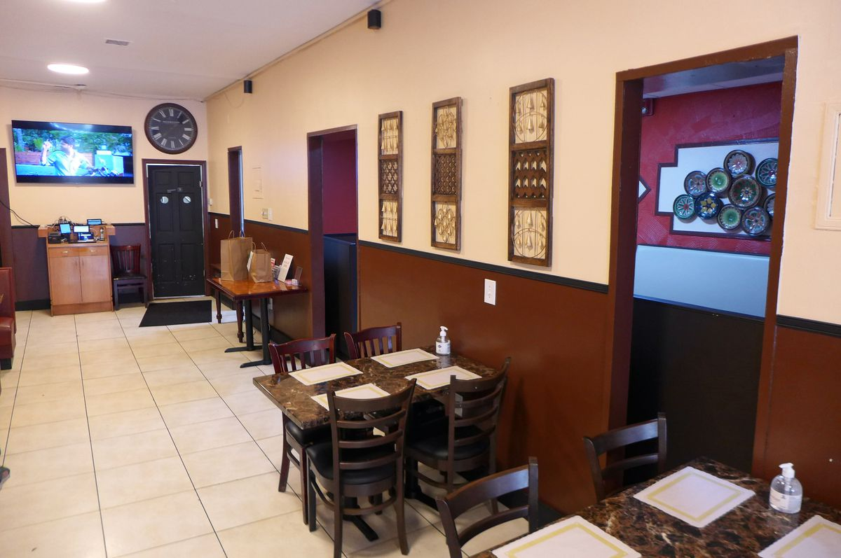 A pinkish room with brown wainscoting with tables along one wall and a big screen TV at the end.
