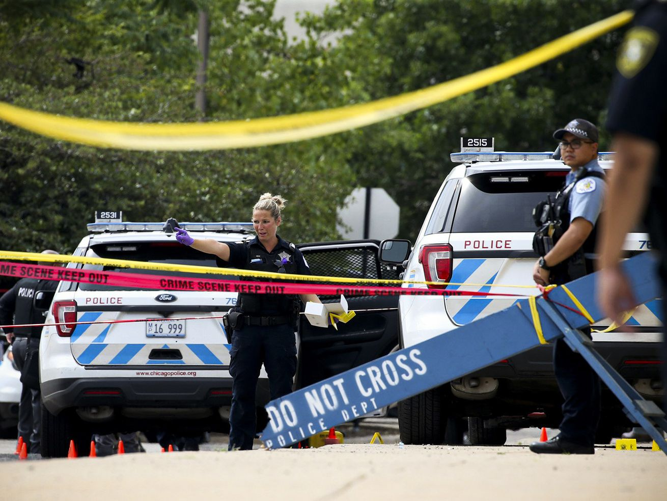 "Police vehicles and officers seen behind lines of caution tape and a ""do not cross"" barricade."