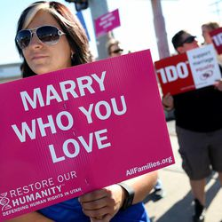 Julie Yunk of Salt Lake City joins about 40 others at a same-sex marriage rally on State Street in Salt Lake City on Tuesday, April 28, 2015.