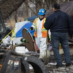 A worker from the city's Department of Streets and Sanitation removes a propane tank while clearing out a homeless encampment near South Desplaines Street and West Roosevelt Road, Monday morning, Feb. 10, 2020.