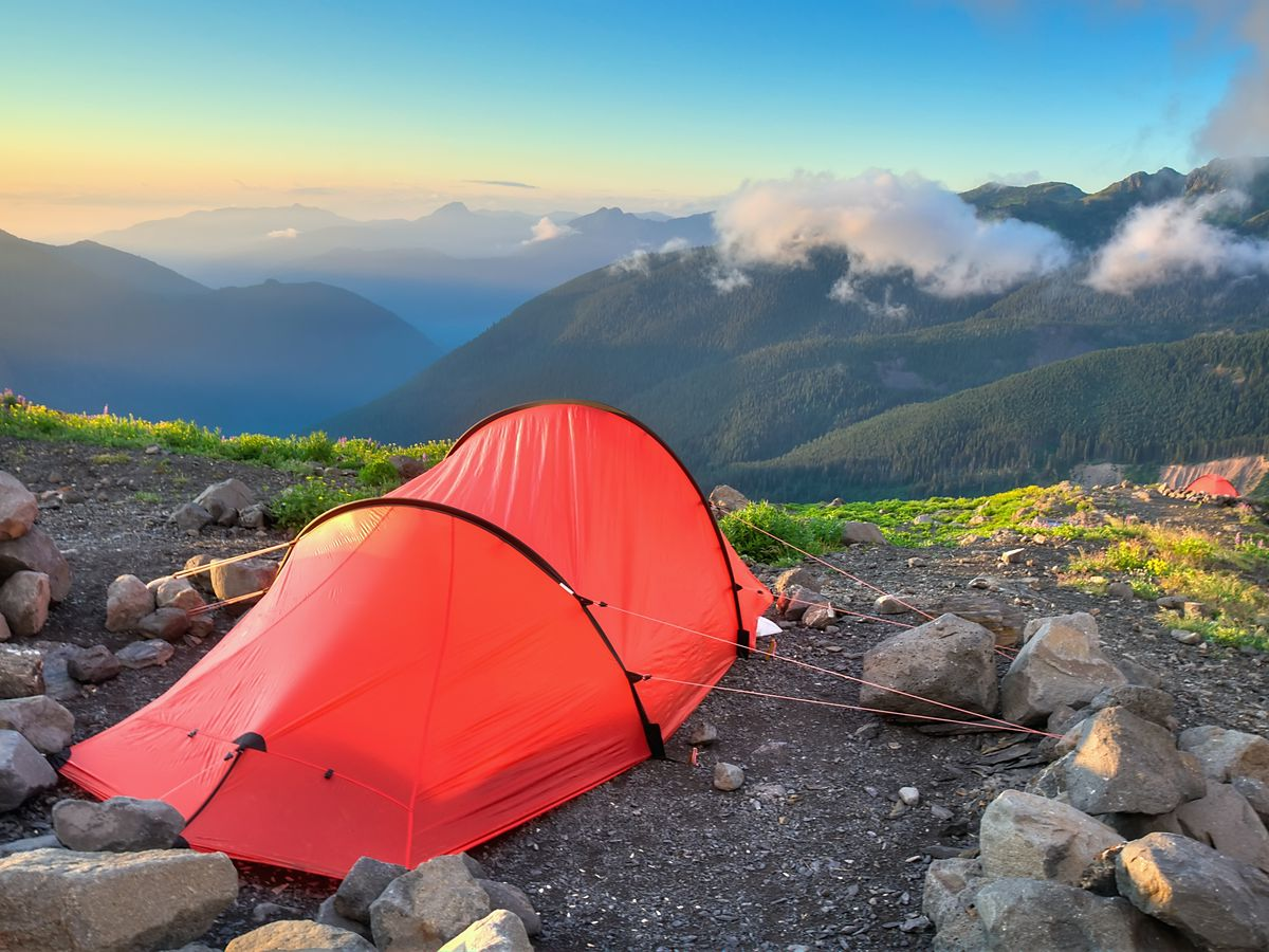 A red tent pitched on a flat, rocky area lined with grass overlooking several mountains.