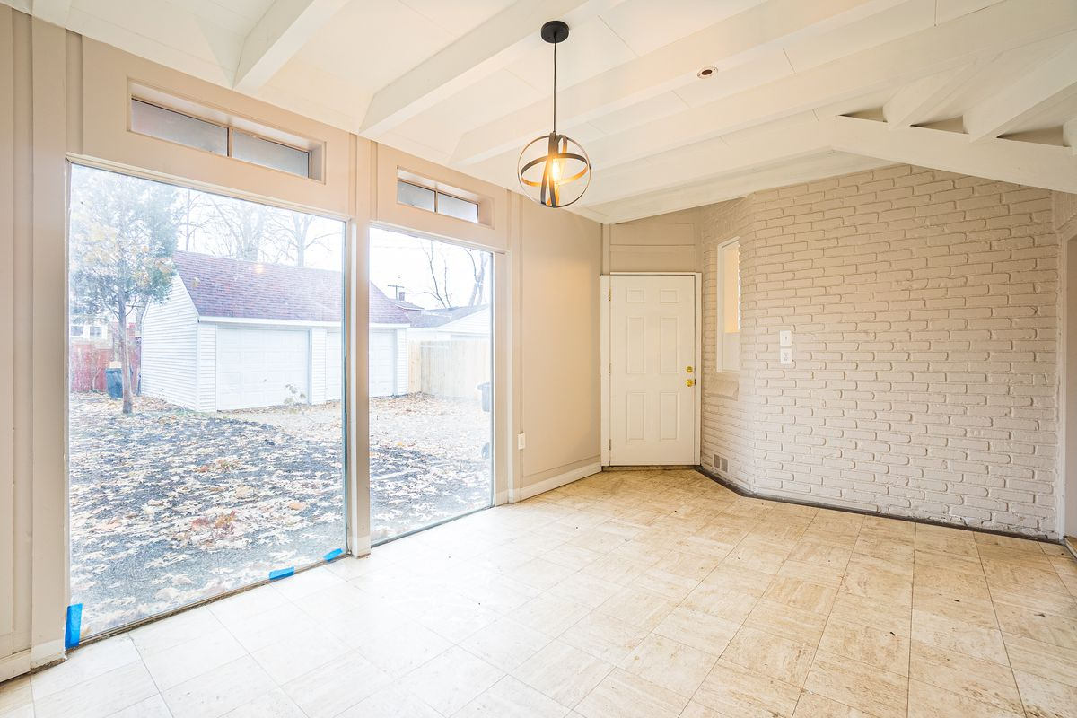 An empty room with laminate floor tiles and white-painted brick walls. Two large windows face the back yard.