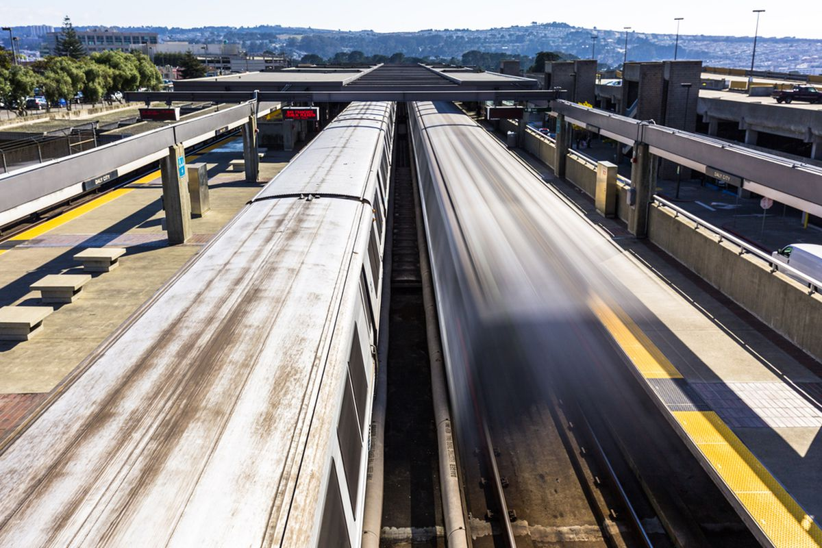 Two trains leaving a BART station, one of them a blurred streak.