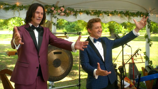 Bill and Ted, standing on an outdoor stage in bright formalwear, prepare to perform a terrible song at a wedding in Bill & Ted Face the Music.