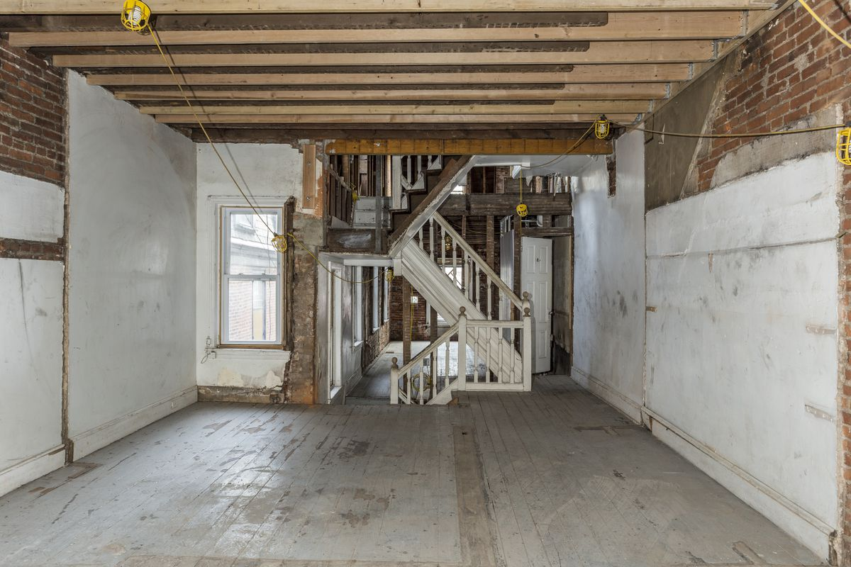 A completely gutted room with a staircase in the center.