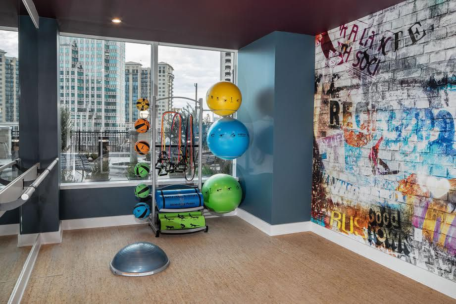 A small gym area with graffiti on the walls.