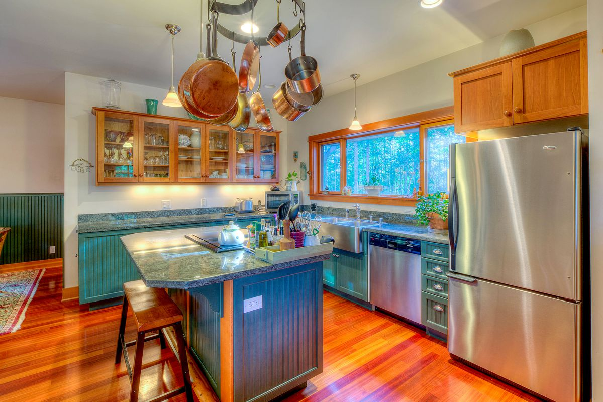 A kitchen with wainscoting wrapped island and cabinets and deep green countertops. Copper pots hang above.