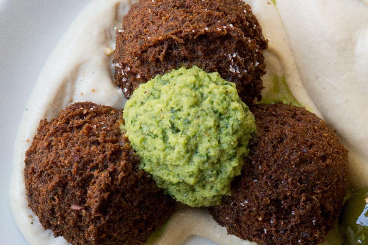A picture of three balls of falafel with a dollop of green shug at Shalom Y'all