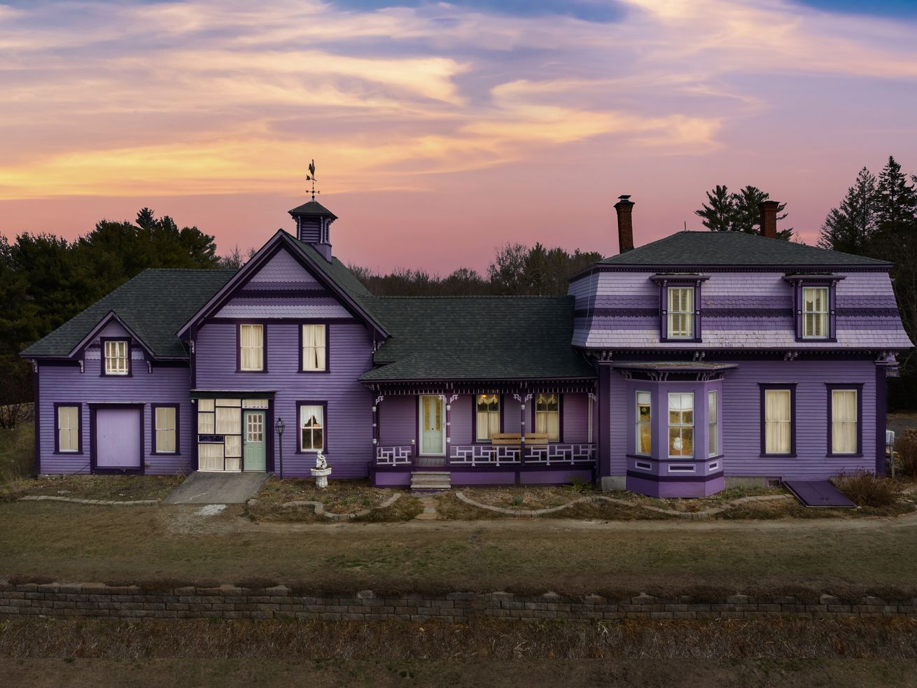 An exterior view of a Victorian house painted in many shades of purple.