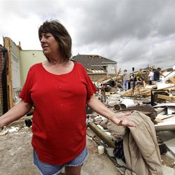 Sherry Enochs, stands in what is left of her home as she recounts the tornado that struck her home Wednesday, April 4, 2012, in Forney, Texas. Enochs was babysitting three children all under the age of 3, when the tornado struck. All survived the storm with minor bumps and bruises.  (AP Photo/Tony Gutierrez)