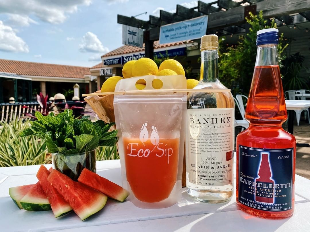 A pouch of a pink cocktail sits on an outdoor table next to ingredients such as watermelon, fresh mint, and two liquor bottles