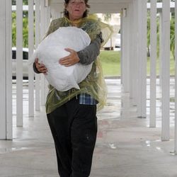Cheri Senecal walks with a bag of personal items to a shelter in Key West, Fla., Saturday, Aug. 25, 2012 as she prepares for Tropical Storm Isaac, Saturday, Aug. 25, 2012. Isaac's winds are expected to be felt in the Florida Keys by sunrise Sunday morning. (AP Photo/Alan Diaz)