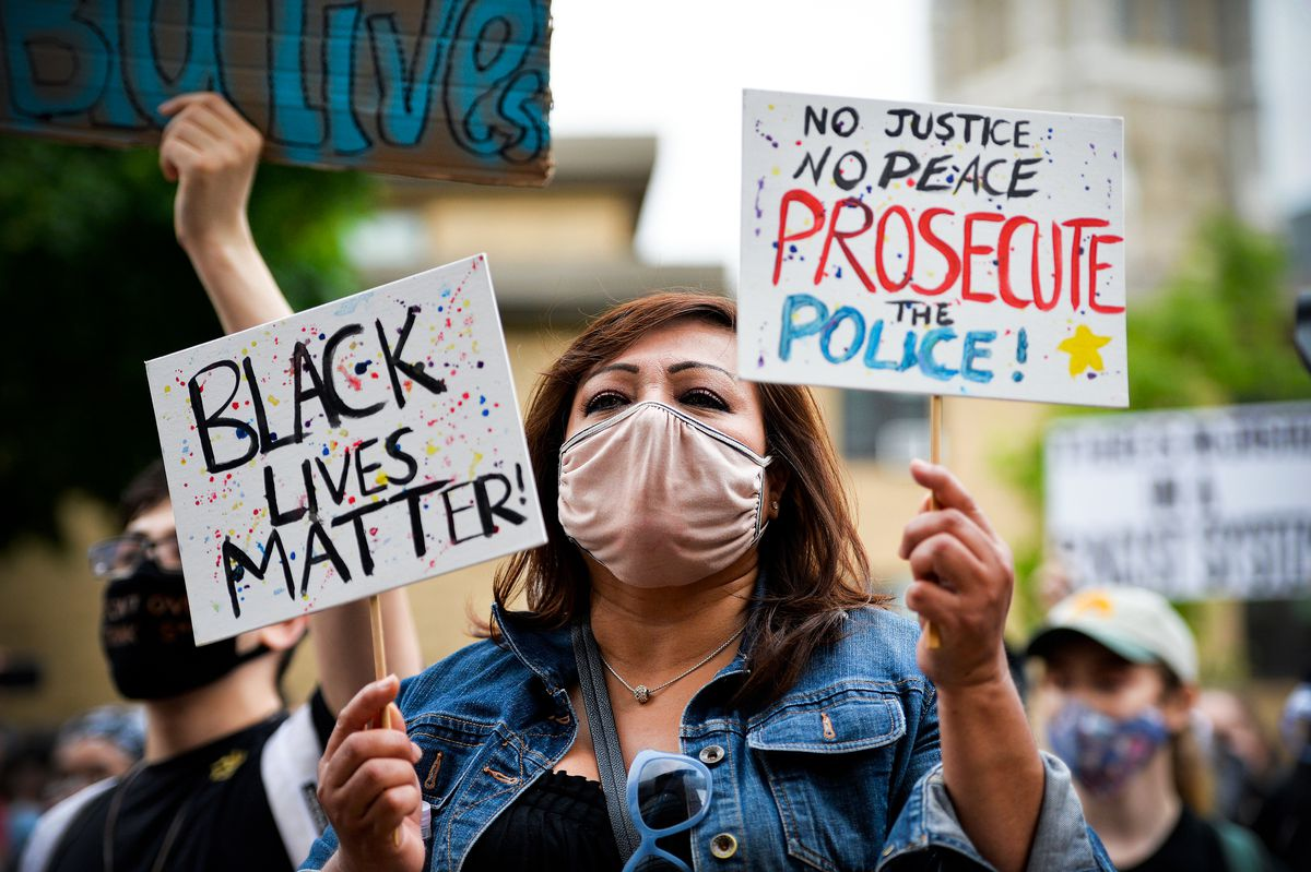 "A woman in a taupe mask holds two small signs flecked with colorful paint. ""Black Lives Matter,"" one reads; the other, ""No justice, no peace prosecute the police!"""