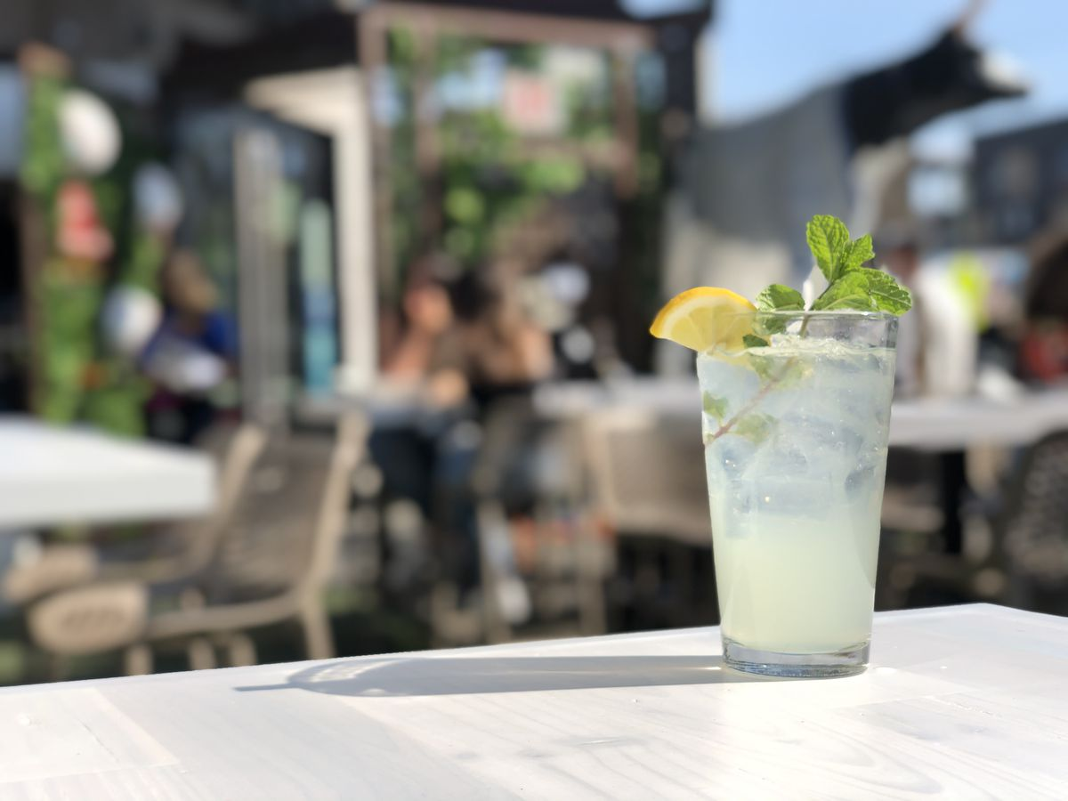 A light yellow cocktail with a sprig of mint and a lemon slice on a table outdoors