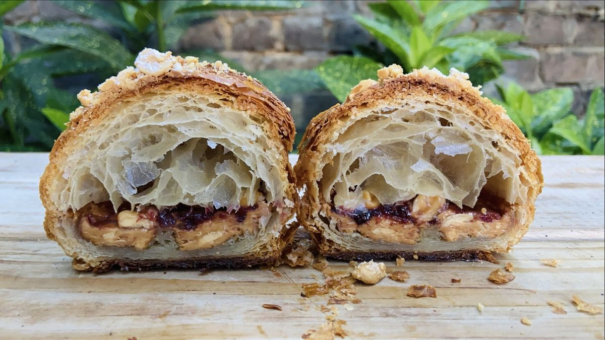 A cross section of a croissant with peanut butter and raspberry jelly oozing down the middle.