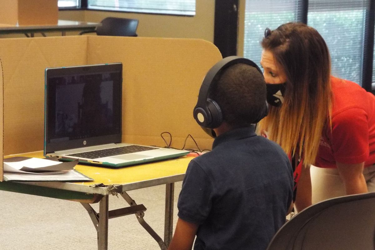A Shelby County Schools student gets assistance from a staffer as he works remotely from the YMCA's virtual learning center in Cordova on the first day of school.