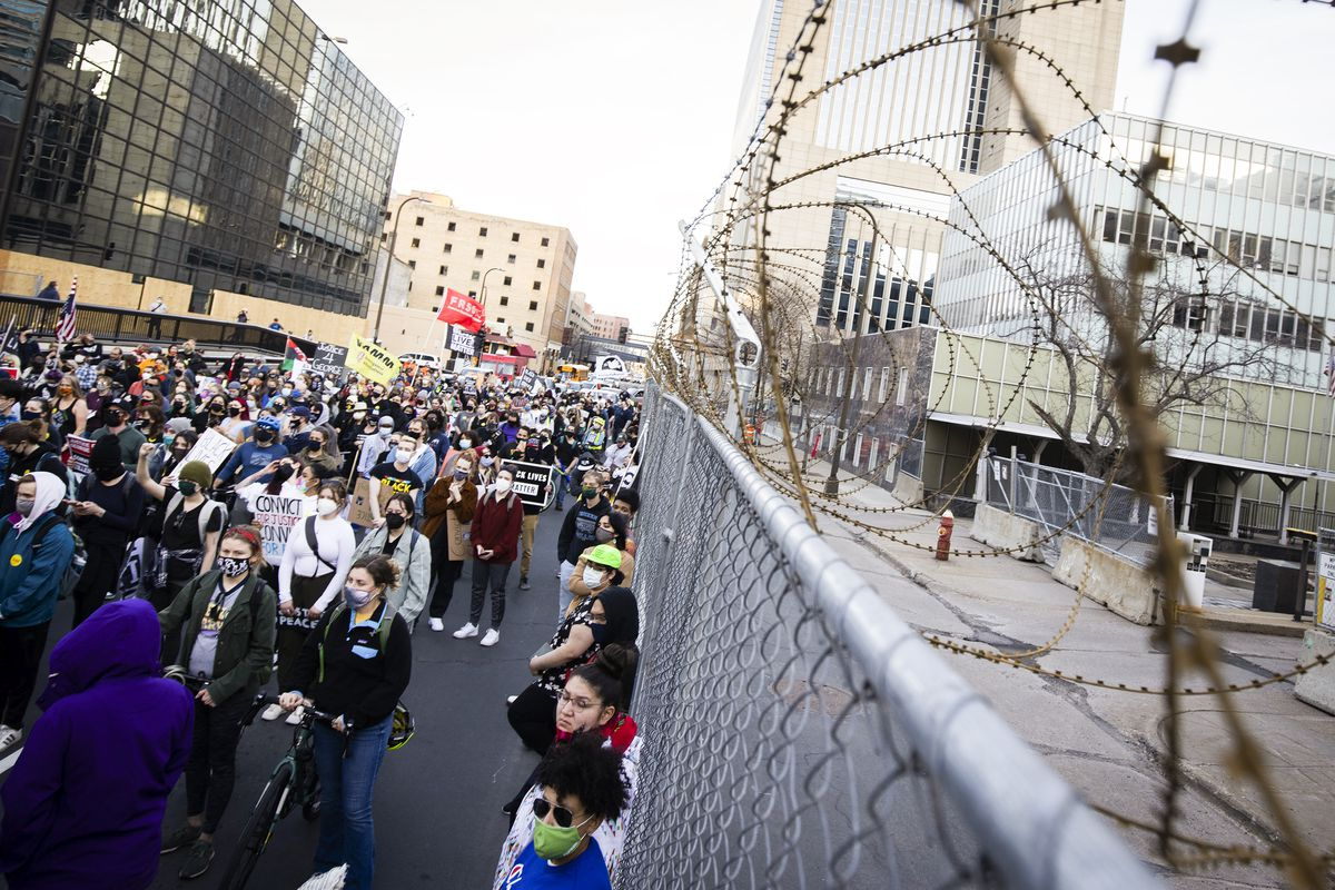 A mass of people, mostly masked, march next to a tall chain link fence topped with barbed wire.