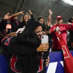 San Diego State offensive lineman Chris Martinez (64) celebrates with a fan after a 33-31 win in triple overtime against Utah in an NCAA college football game Saturday, Sept. 18, 2021, in Carson, Calif.