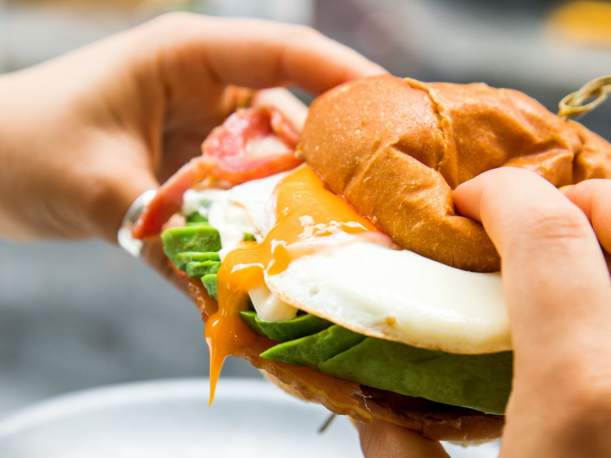 person holding breakfast sandwich with oozing egg and avocado inside