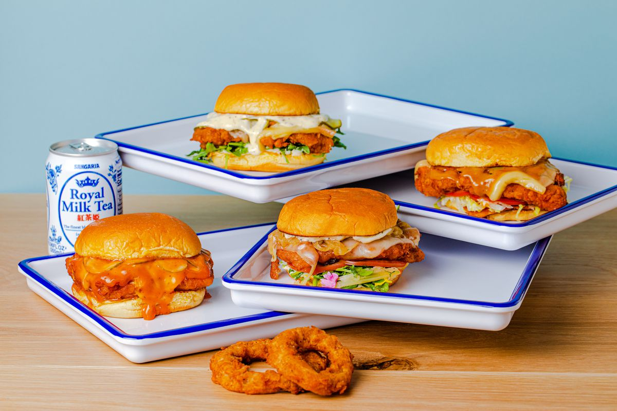 A stack of burgers and other sandwiches on white metal trays with blue edges.