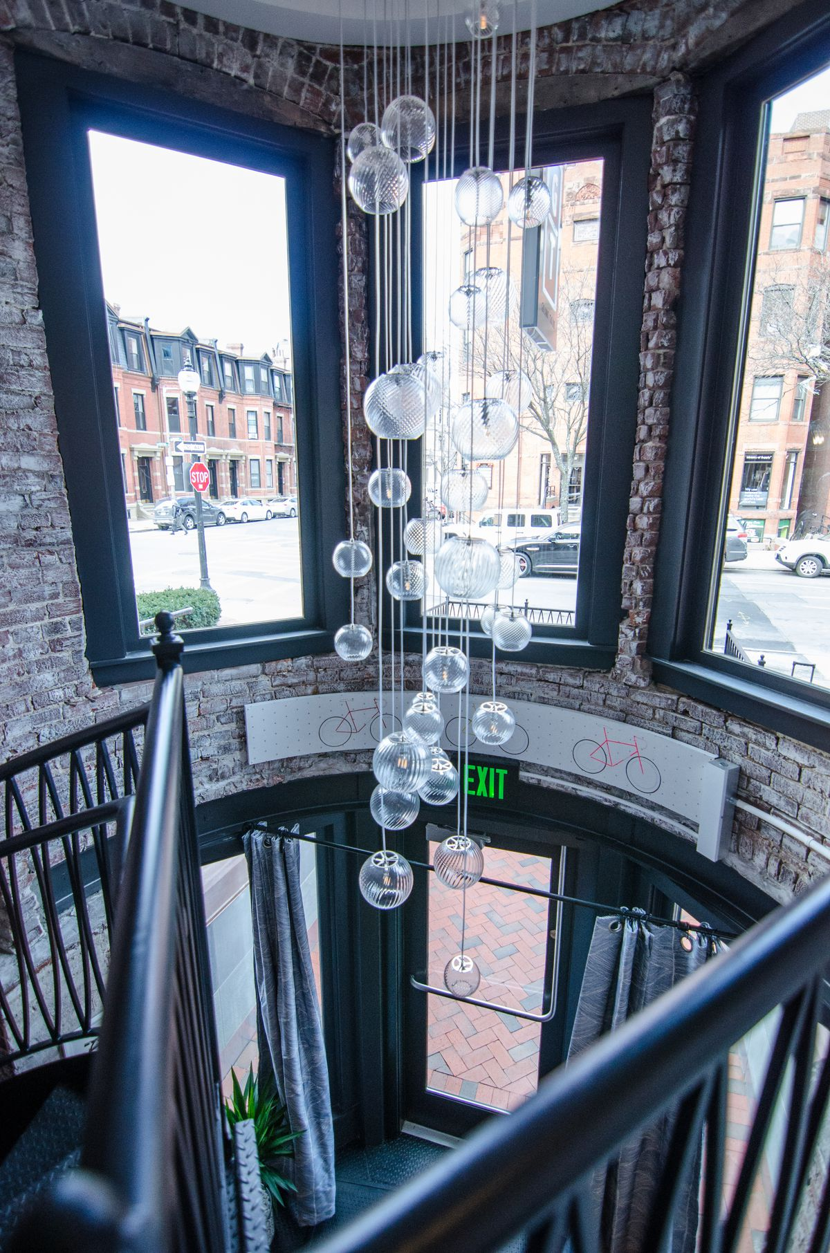 A glass globe light fixture dangles down a two-story restaurant space with white-washed brick walls. The city street is visible through large windows.