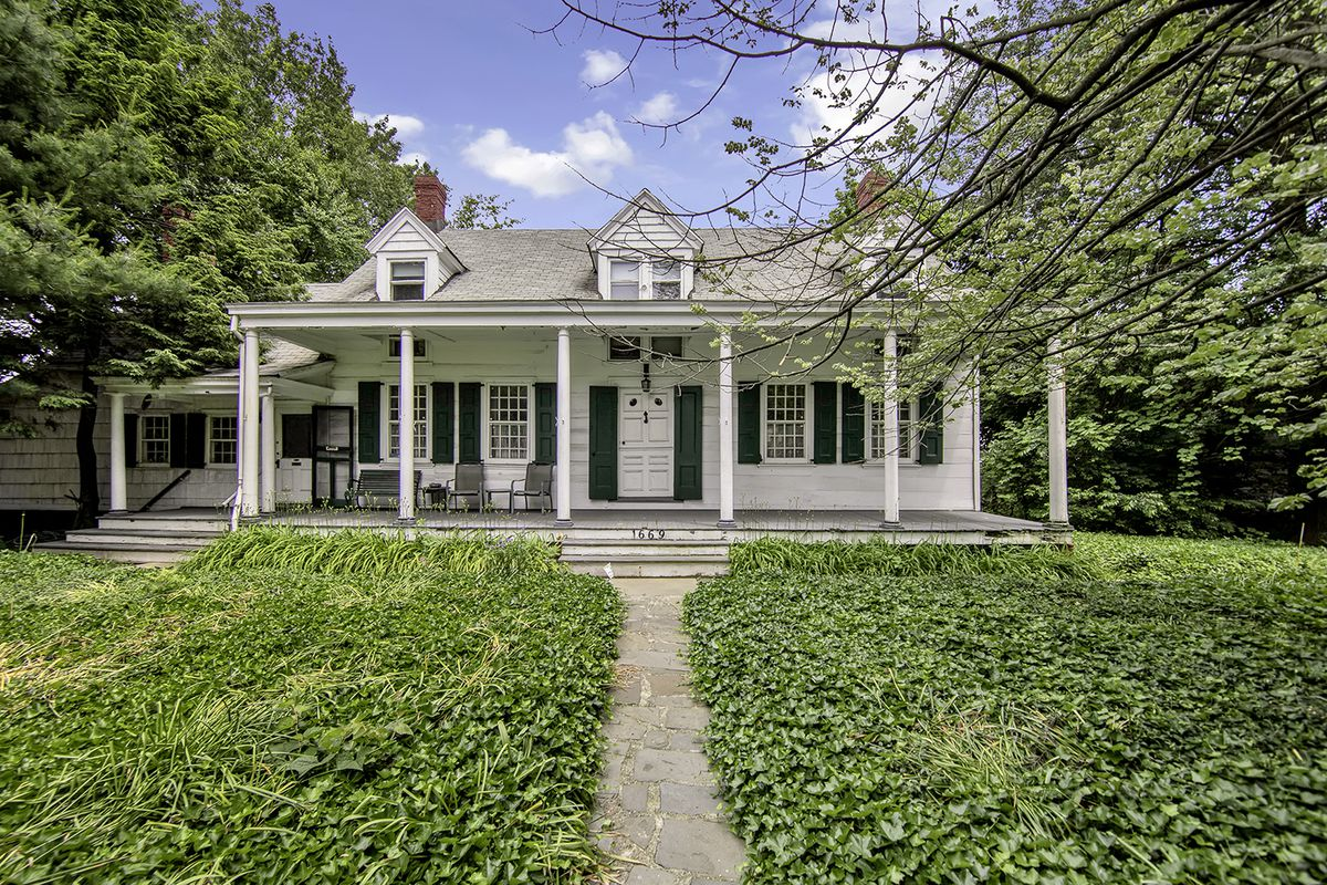 A farmhouse with a large front garden, and a porch with columns.