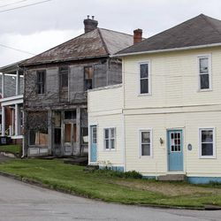 In this April 16, 2012 photo, a freshly painted yellow home is shown  in Glouster, Ohio. Building by building,  volunteers are trying to perk up their Athens County village of 2,000, hoping that a little cosmetic work can boost the community's spirit.