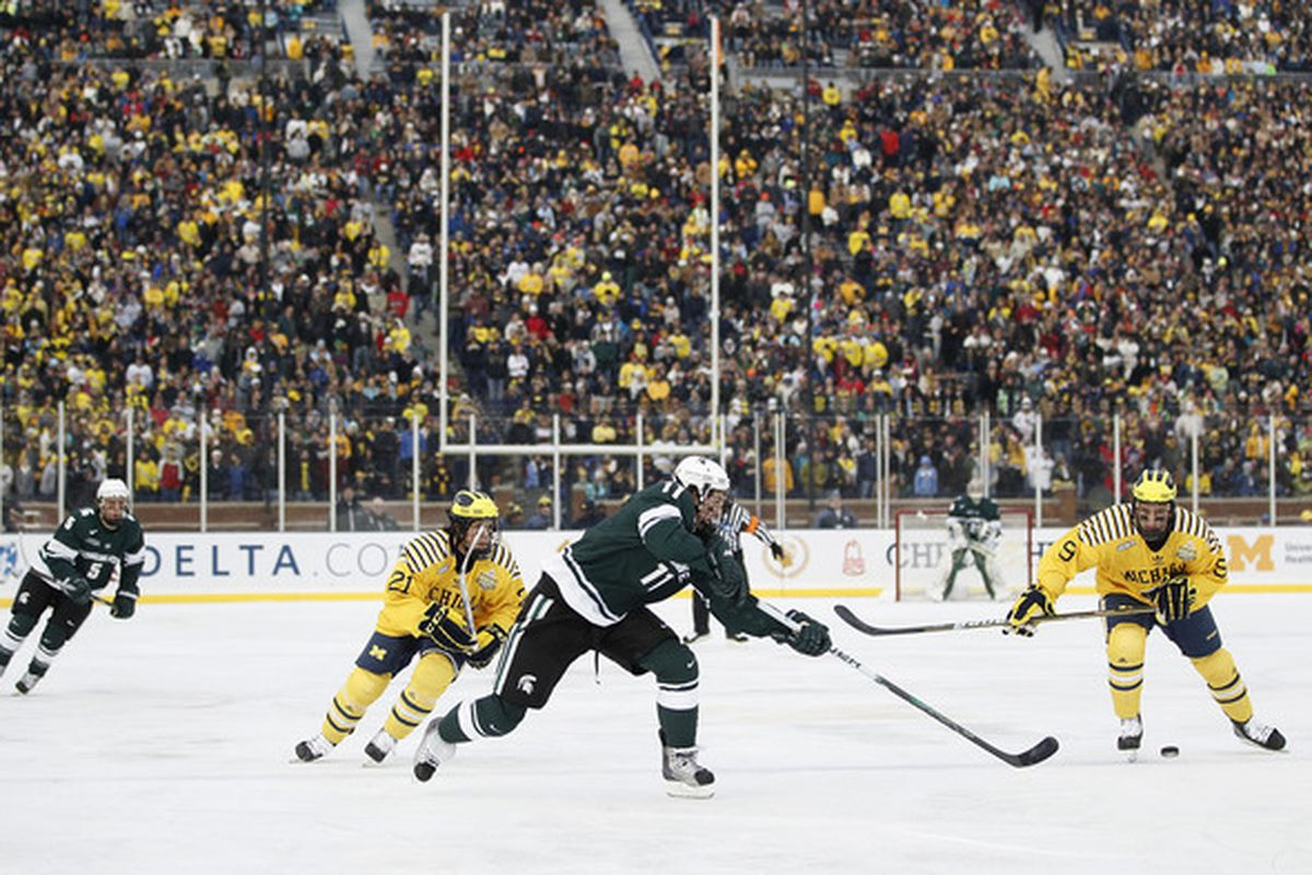 Brett Perlini #11 of the Michigan State Spartans passes to a teamate in front of A.J. Treais #21 and Luke Moffatt #9 of the Michigan Wolverines at Michigan Stadium on December 11 2010 in Ann Arbor Michigan.  (Photo by Gregory Shamus/Getty Images)
