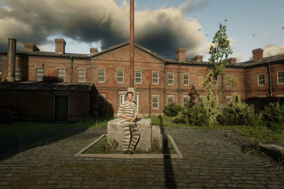 Red Dead Online - a player in a striped prison uniform poses in front of the in-game prison Siskia Penitentiary.