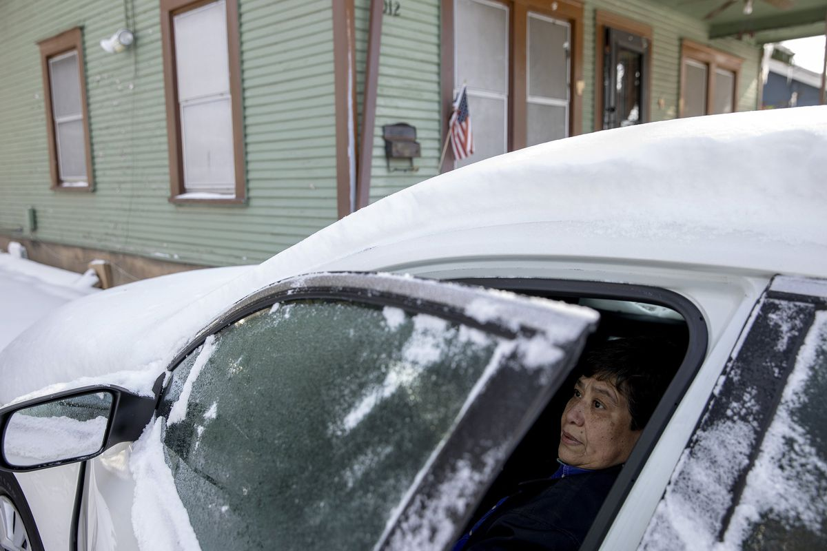 Maria Pineda warms up in her car outside her home on Garden Street in East Austin, Texas, Tuesday Feb. 16, 2021, during a power outage caused by a winter storm. Pineda said her home has been without power since early Monday morning.