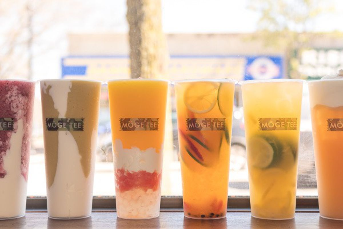 Cups of boba tea lined up against a window