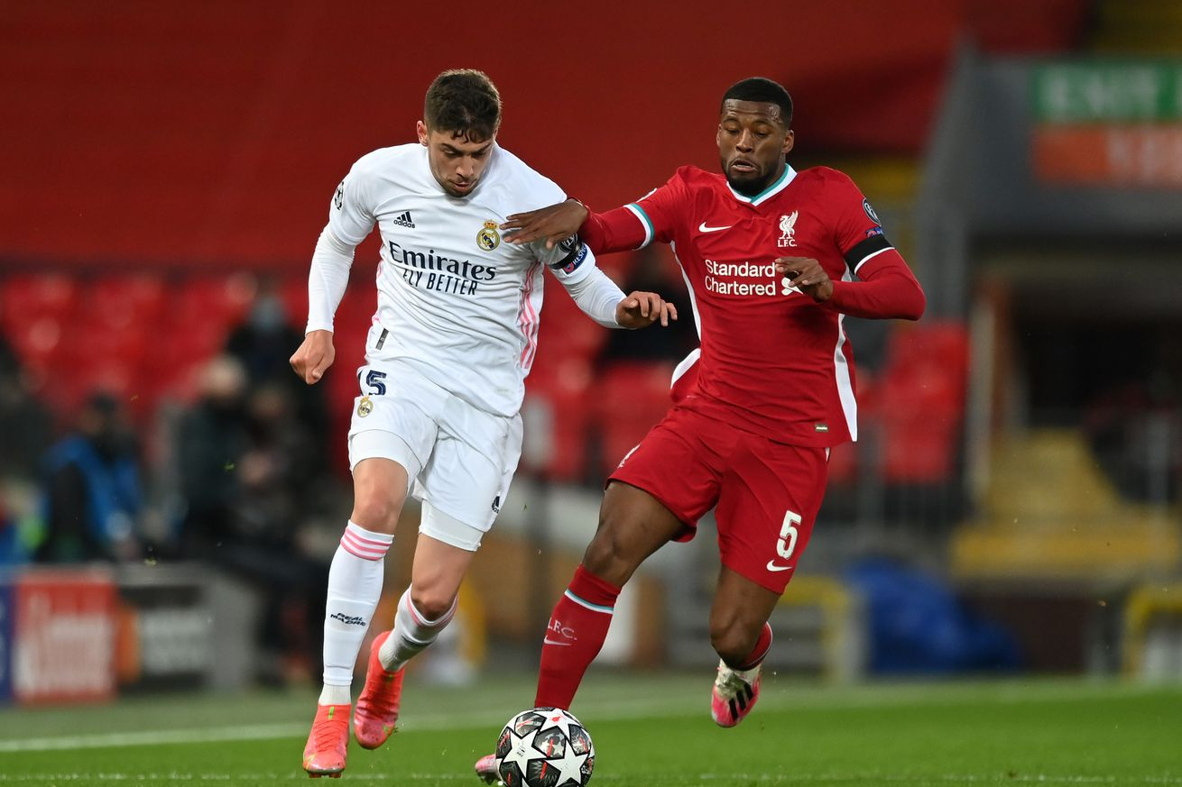 Federico Valverde of Real Madrid is challenged by Georginio Wijnaldum of Liverpool during the UEFA Champions League Quarter Final Second Leg match between Liverpool FC and Real Madrid