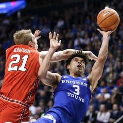 Brigham Young Cougars guard Elijah Bryant (3) falls as he goes for a layup against Utah Utes forward Tyler Rawson (21) at the Marriott Center in Provo on Saturday, Dec. 16, 2017.