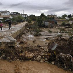 Residents walk on a muddy street after heavy rain caused flash floods in the town of Villanueva del Rosario, Malaga, southern Spain, Friday, Sept. 28, 2012. Homes were destroyed and at least one woman was killed. Rescue workers are searching to determine if there are more victims.