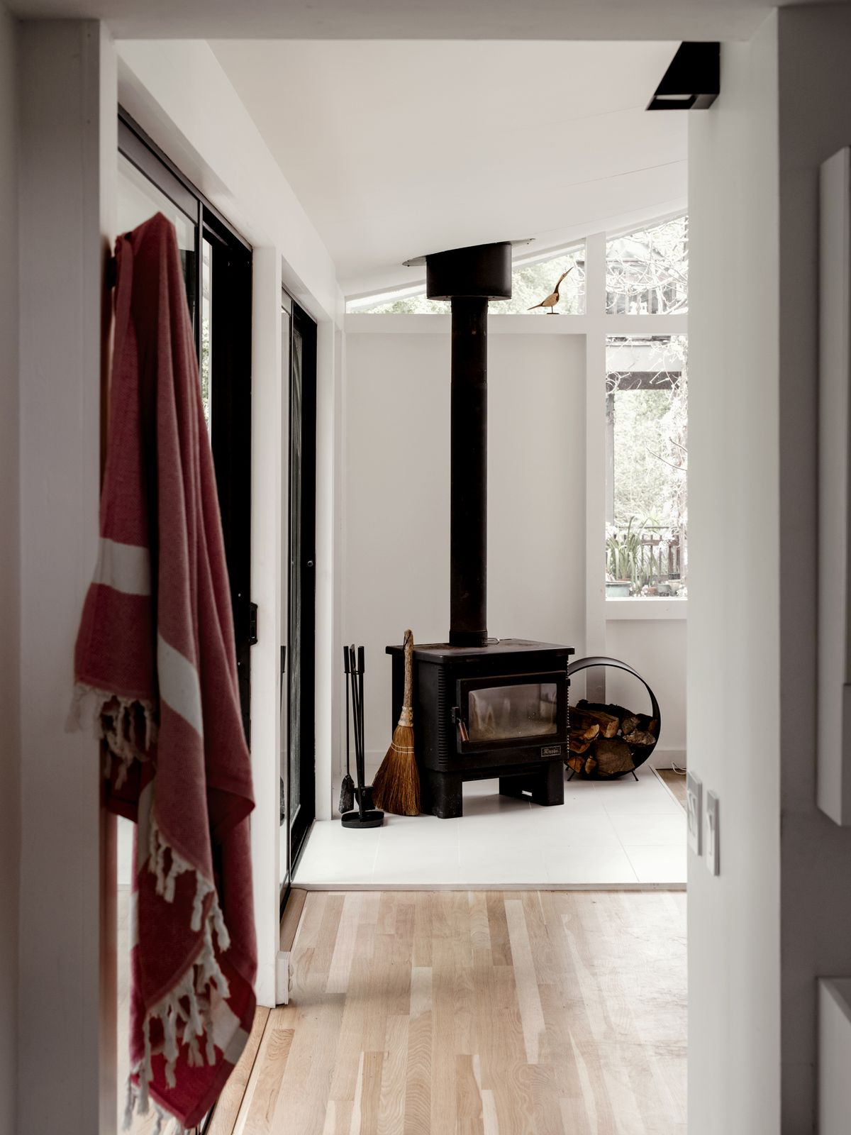 The corner of a living room. There is a black fireplace. The floor is hardwood and the walls are painted white.