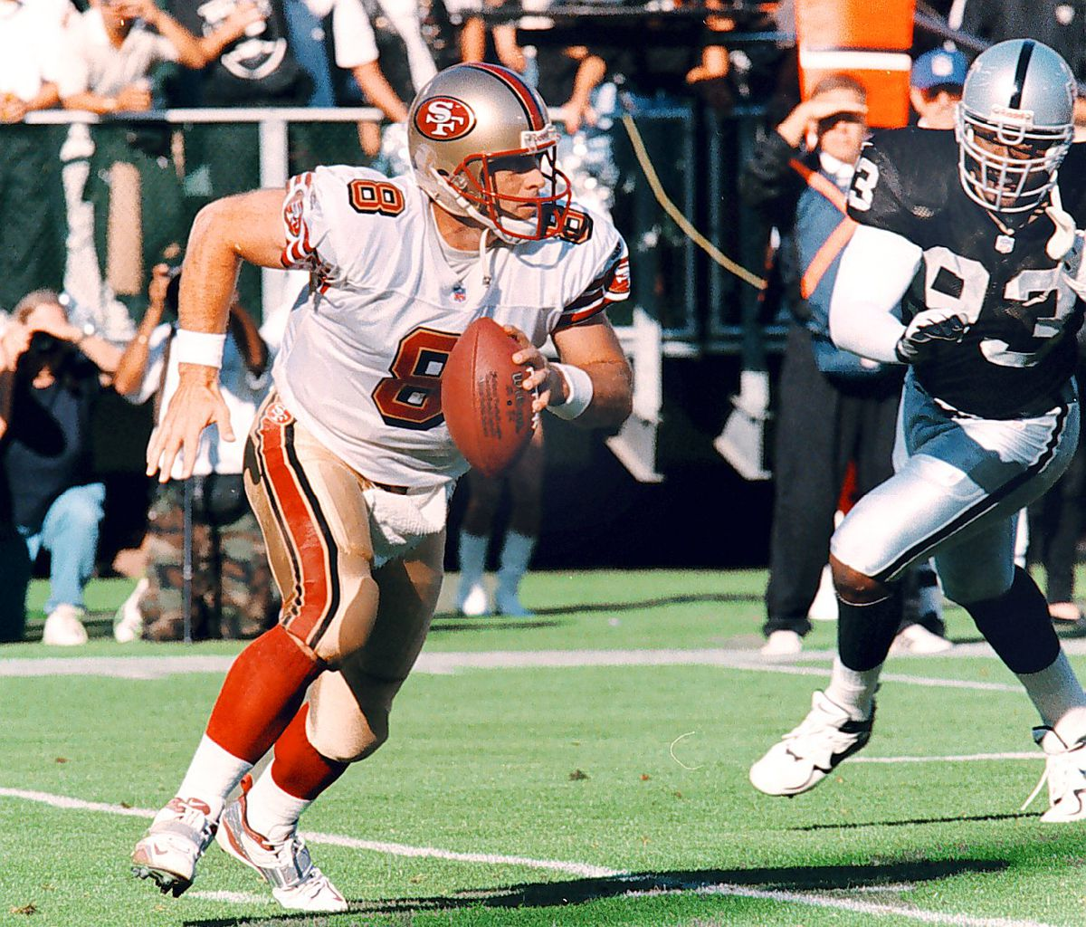 Oakland, CA August 30, 1999: San Francisco quarterback Steve Young is chased by Oakland Raider defensive end James Harris in the first quarter. Young ran for a first down. (Ron Riesterer/Oakland Tribune)